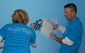 Design Angels volunteers Annette and Kevin Kuester apply a racing flag decal on the bedroom wall