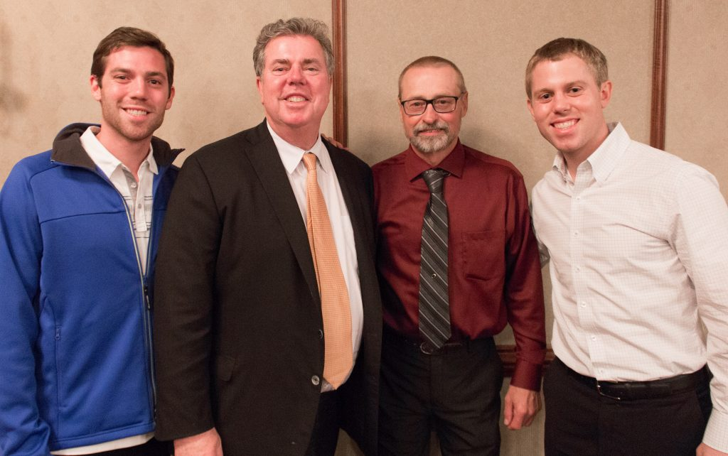 Chuck VandenLangenberg (third from left) shared memories with members of the Martin family (L-R: Joe, Edward and David) at his retirement party in May 2017.