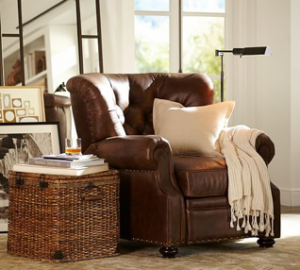 Brown leather couch, white throw pillow and throw blanket, wicker basket side table