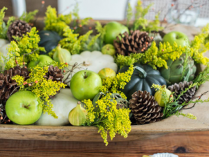 green plants, green apples, and pine cones make the perfect centerpiece for a fall table
