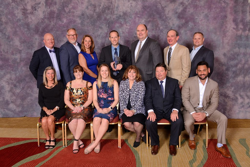Gary VandenLangenberg (2nd row, center) and Rachel Weber (1st row, third from left) of H.J. Martin & Son were joined by vendor partners in accepting the award.