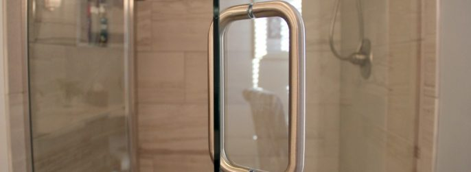 Glass shower door with a silver shower handle.