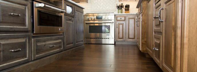 Brown luxury vinyl plank kitchen flooring with a glossy white backsplash.