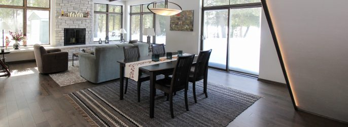 Brown dining room hardwood flooring with a dark wood dining table and a stone fireplace
