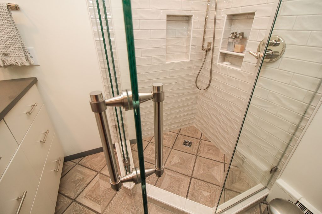White and glossy brick tiled shower with tan mosaic tile flooring