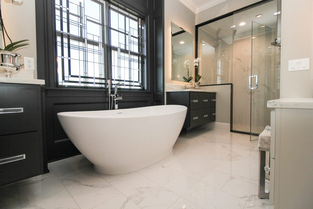 Bathroom with white tile floor, large white bathtub, and black cabinets