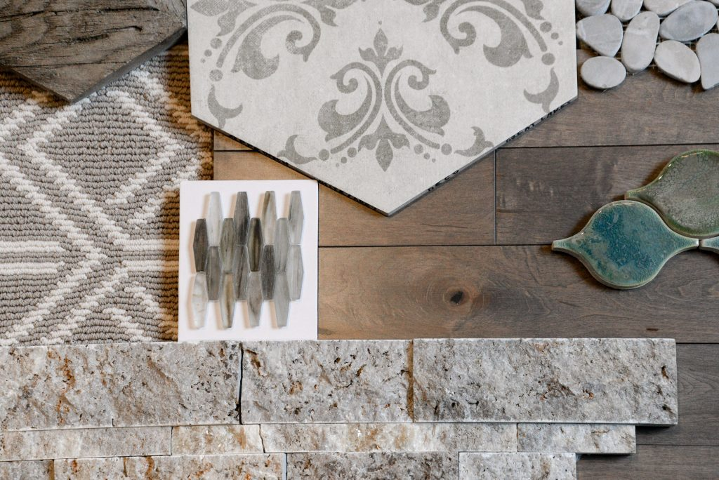Gray tile, brown hardwood, green tile and gray patterned carpet in a mood board.
