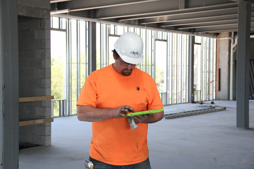 Paperless building plans held by man in hardhat and orange shirt.