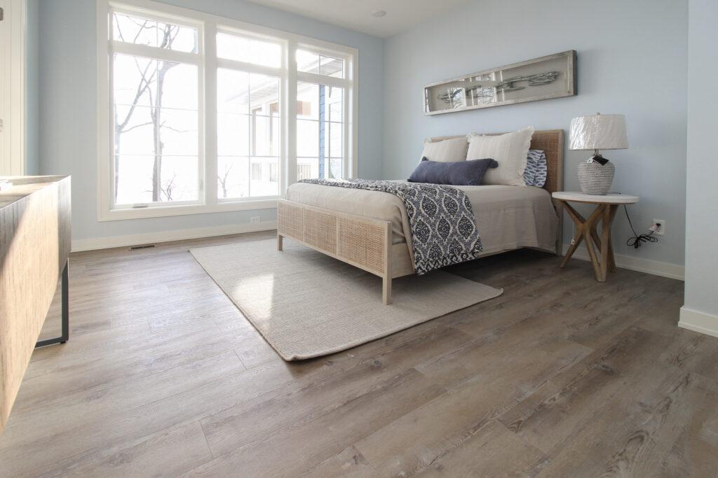 beige hardwood flooring in a light blue bedroom with beige area rug and beadspread