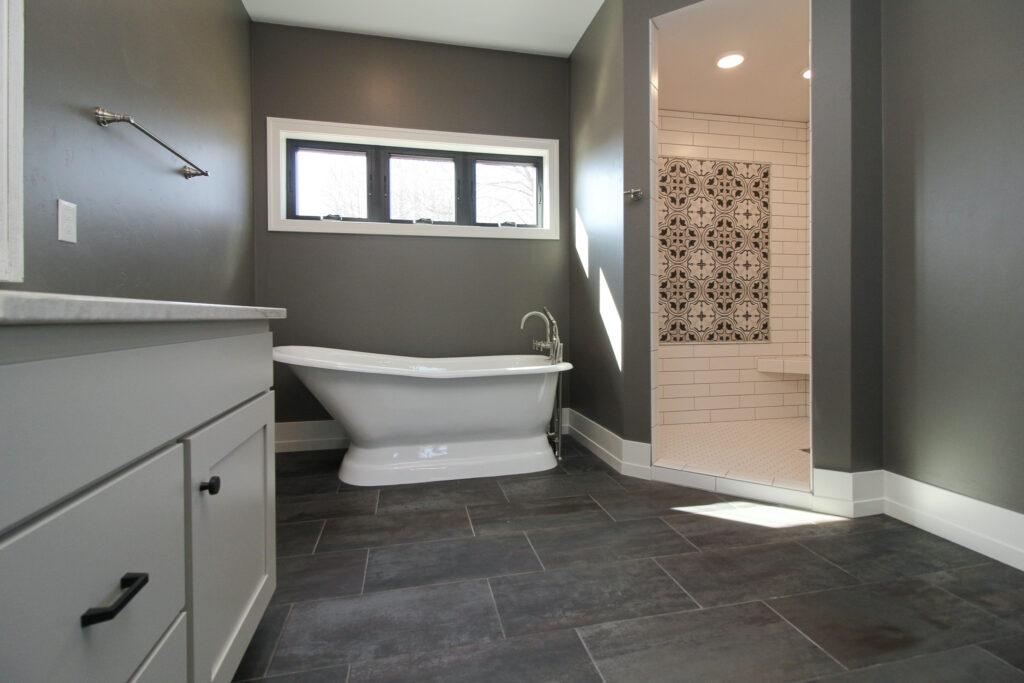 gray bathroom with black tiled floors, white tile shower and white bathtub