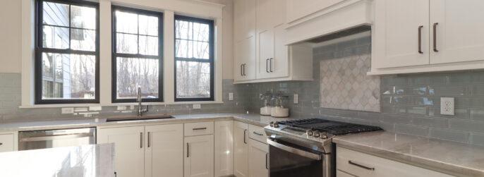 Blue glass kitchen backsplash with white cabinetry