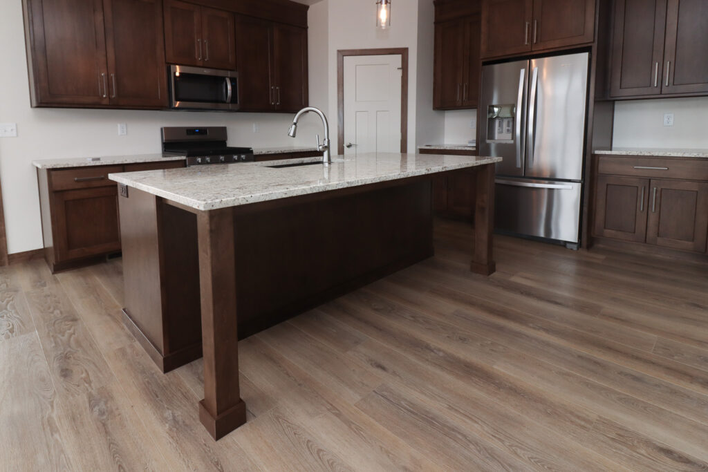 wood look luxury vinyl plank flooring in kitchen with dark cabinets and white counters
